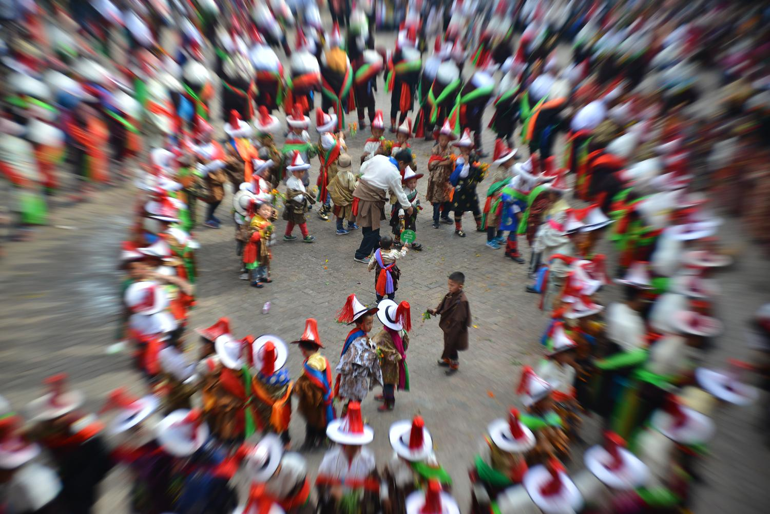 """During the """"Dance"""" or Gar (གར) portion of the festival, men and women wear fine clothes and jewelry and dance together in a swirling pattern. They eventually fill the entire courtyard."""