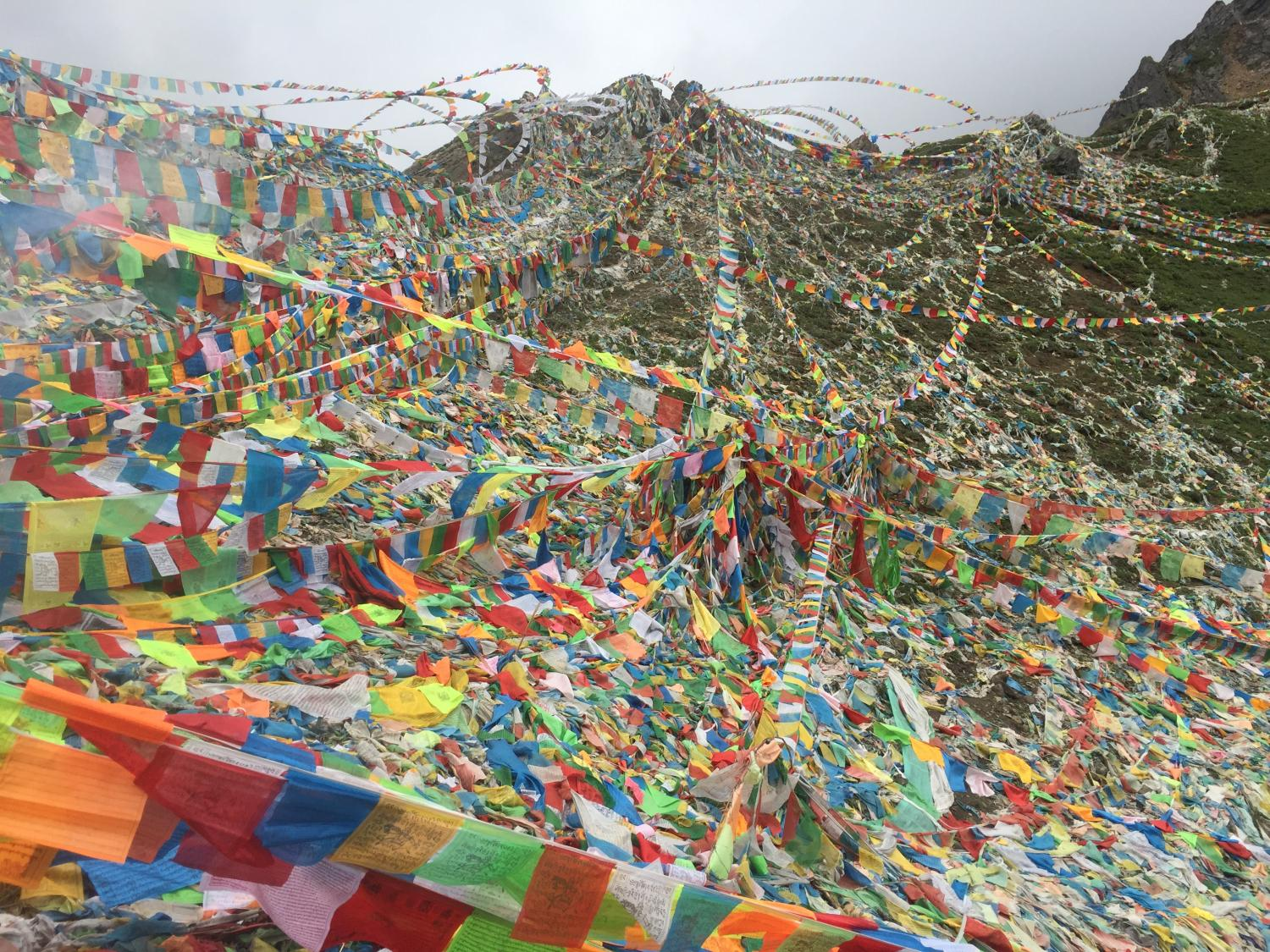 Prayer flags at the top of Dokela. In addition to the standard five colored prayer flags, there are many white prayer flags printed simply with Om mani padme hum, and on which a deceased person's name is written.