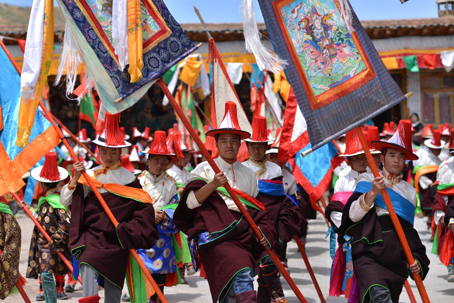 Wey La (be lha བེ་ལྷ) begins the final day of Lurol. Men march in the temple courtyard holding flags, spears, and paintings of deities.