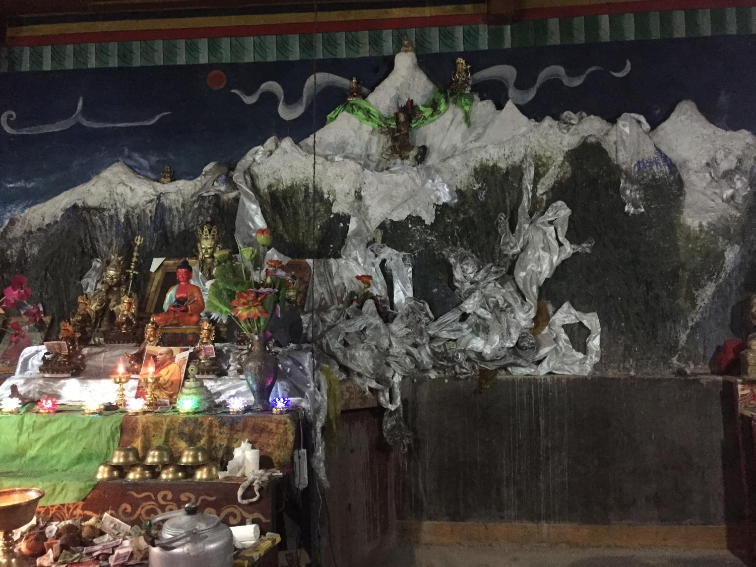 Sonam Norbu built a small temple, in which is this wall sculpture of the entire mountain range around Khawakarbo, to atone for his past sins as a hunter. It is located by a remarkable old grove of ancient cypress trees on the banks of the Mekong River at the edge of Bu Village.