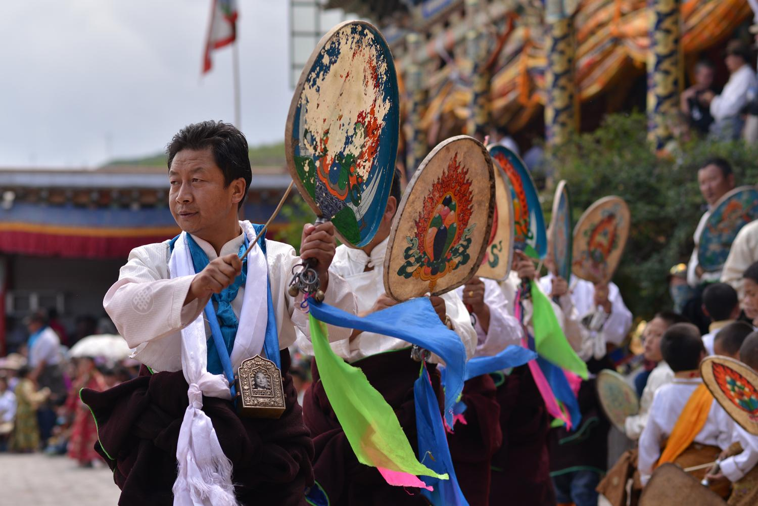 """Men perform La tsey (Lha rtsed ལྷ་རྩེད), or """"God Play,"""" by beating small drums while moving in a rhythmic regimented pattern."""