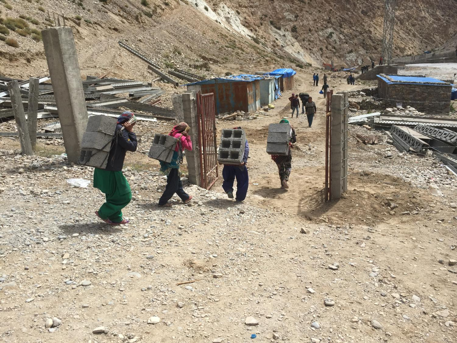 women carrying construction materials across the border