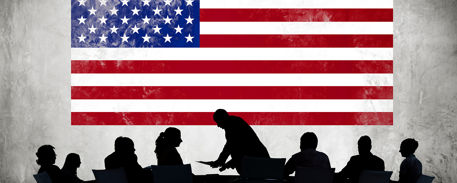 American flag with silhouettes of business people working