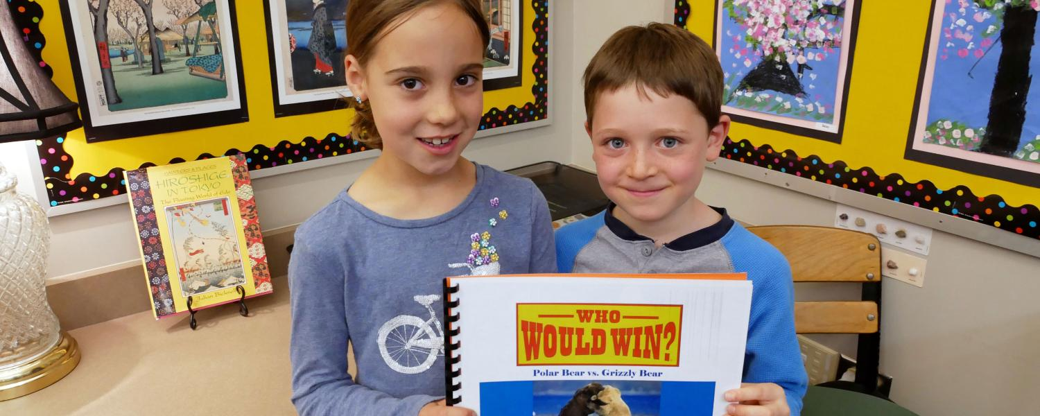 Boy and a girl holding a book in the writing class