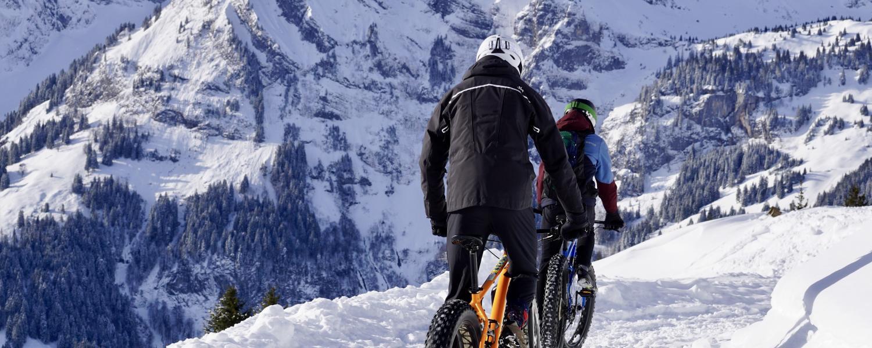 People mountain biking in snow