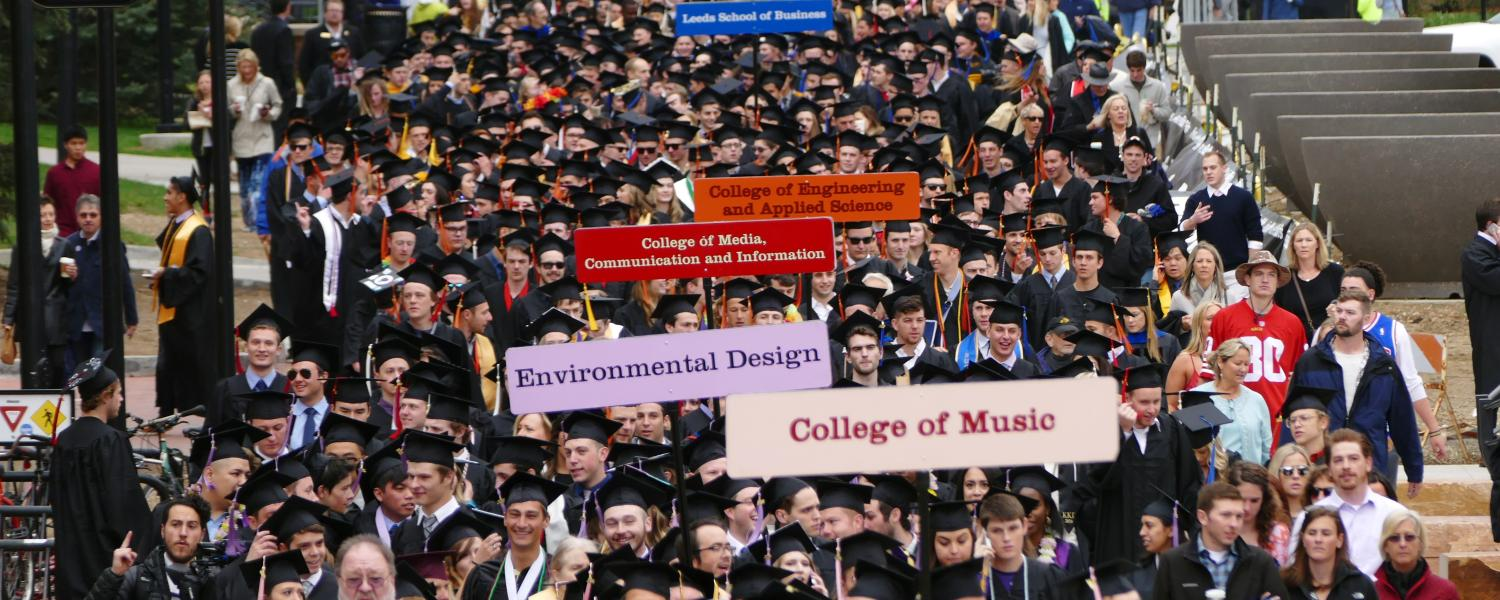 Graduation procession with signs designating each college