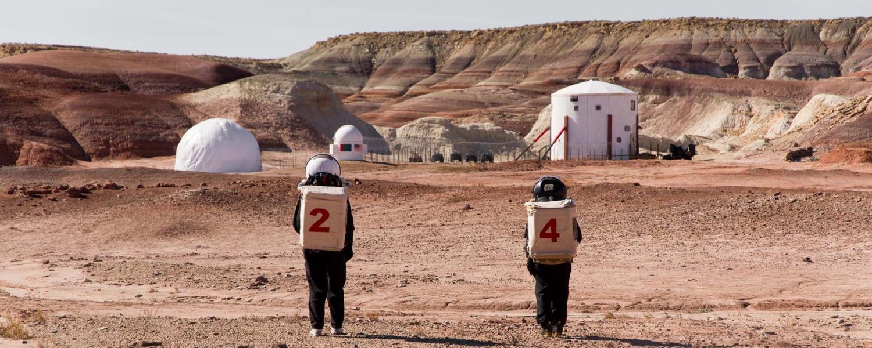 Two people wearing spacesuits walk through the Utah desert