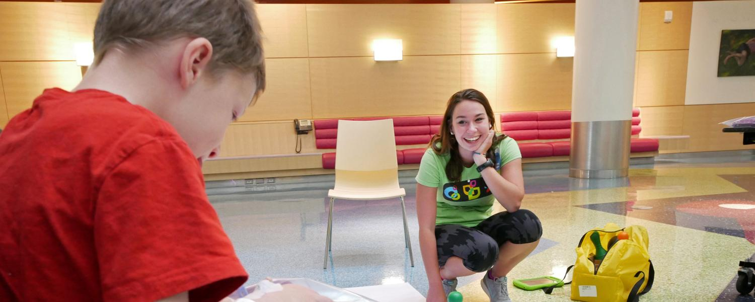 A CU student watches a patient at STEAM Camp control robots using a tablet.