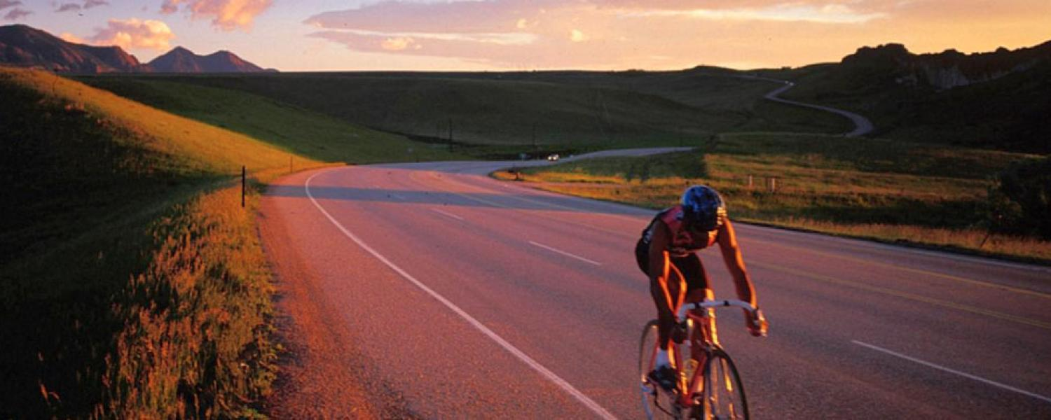 Cyclist on open road with sunset in the background