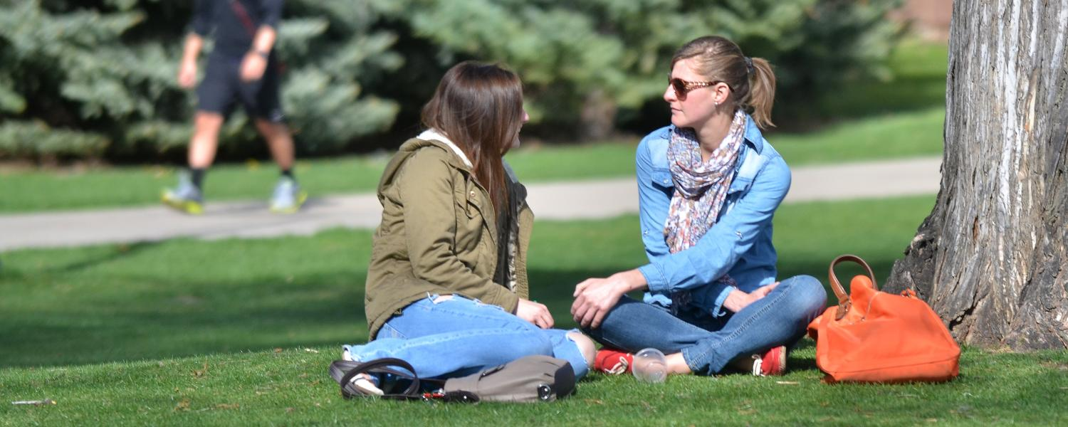 Two students chat sitting on lawn