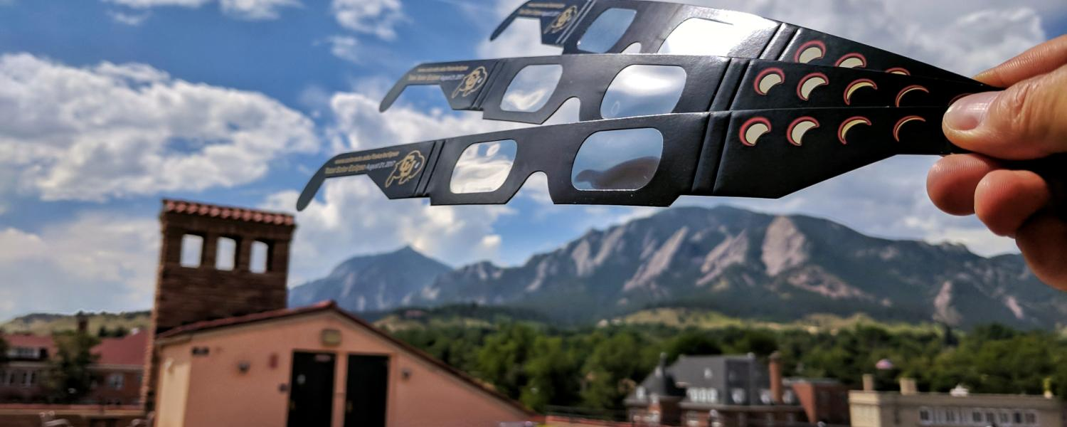 CU Boulder eclipse glasses with Flatirons in distance