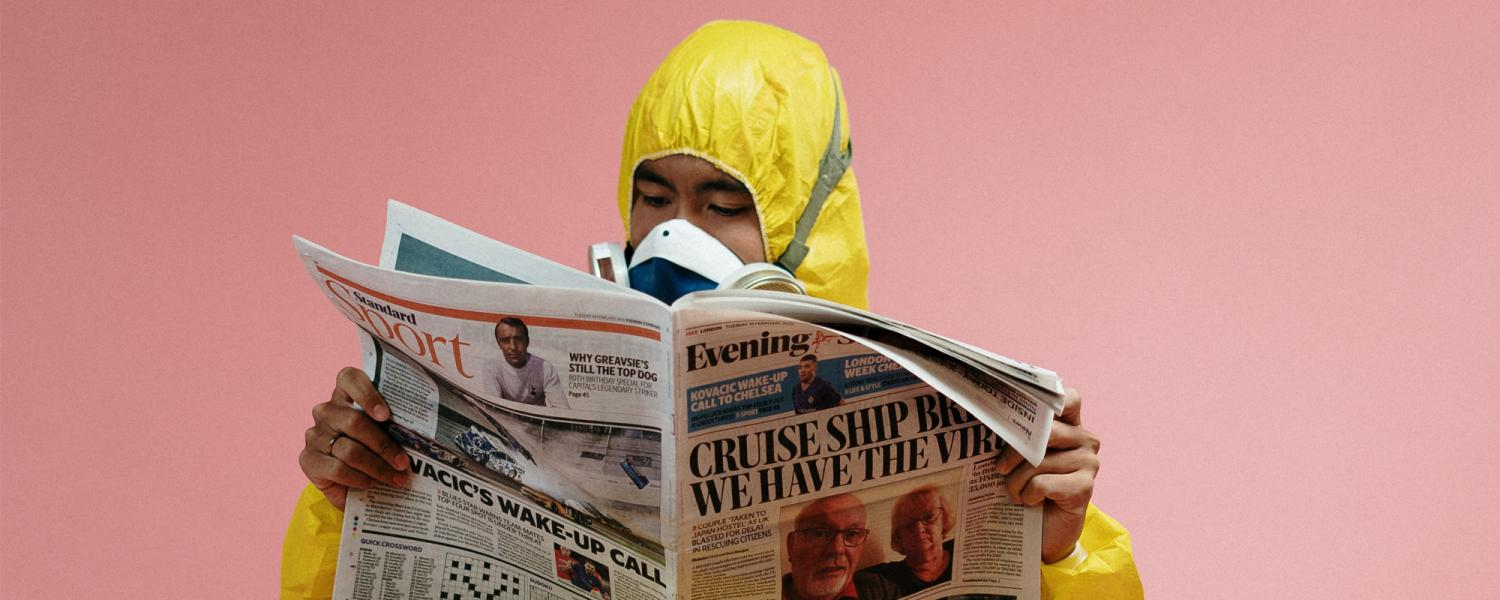 A stock image of a man in a hazardous materials suit reading the news.