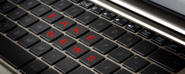 "a keyboard displaying the words ""fake news"""