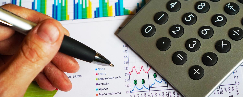 Financial graphs, calculator and pen