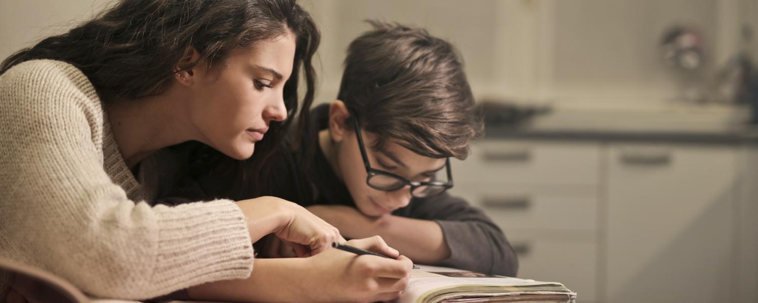 Adult helping young student with homework