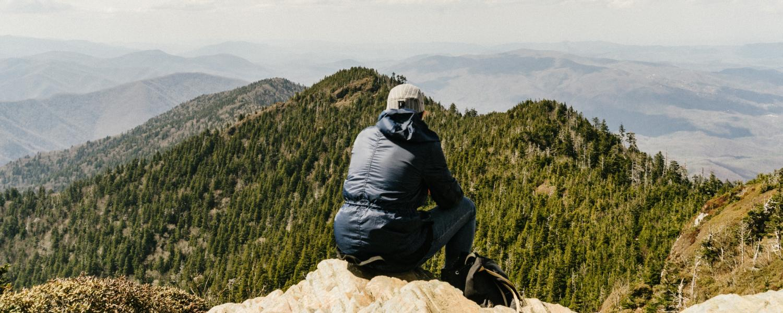Man watches vista from mountain summit
