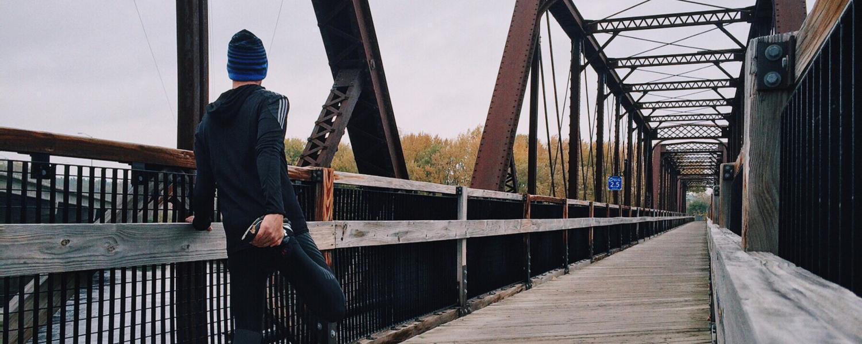 Runner stretches on pedestrian bridge