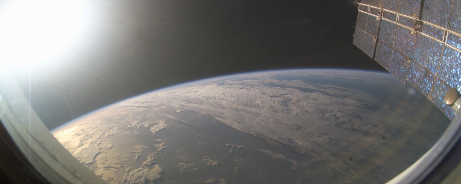 Sun sets over Earth as seen from a window on the International Space Station.
