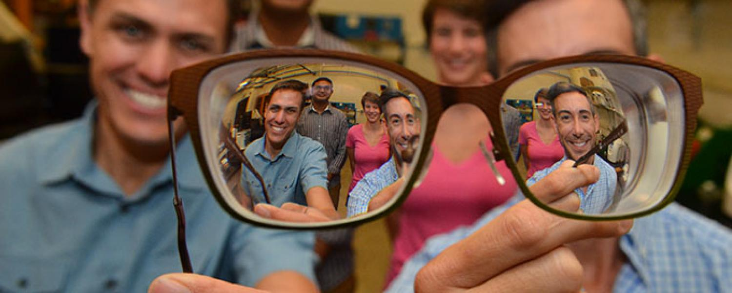 Bart Foster and Wil Srubar look through a pair of eyeglass lenses with graduate research assistants Sankar Ravichandran and Elizabeth Delesky standing behind them.