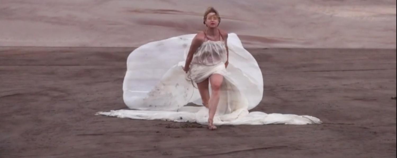 A woman in a white ball gown dances across a sandy expanse
