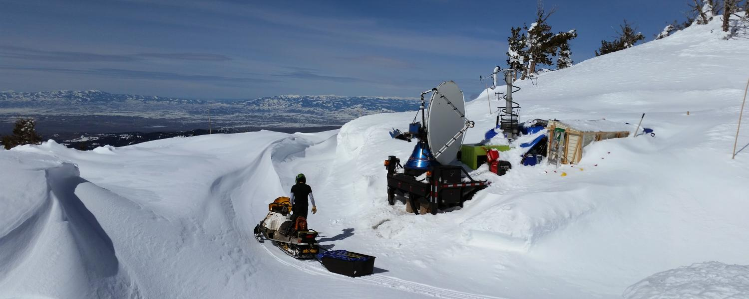 A research dismounts a snowmobile next to a mobile radar dish with a mountain view in the background.