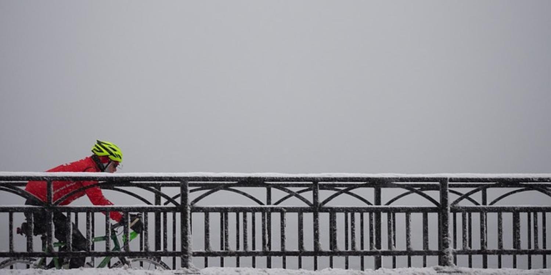 Biker crosses bridge in the winter