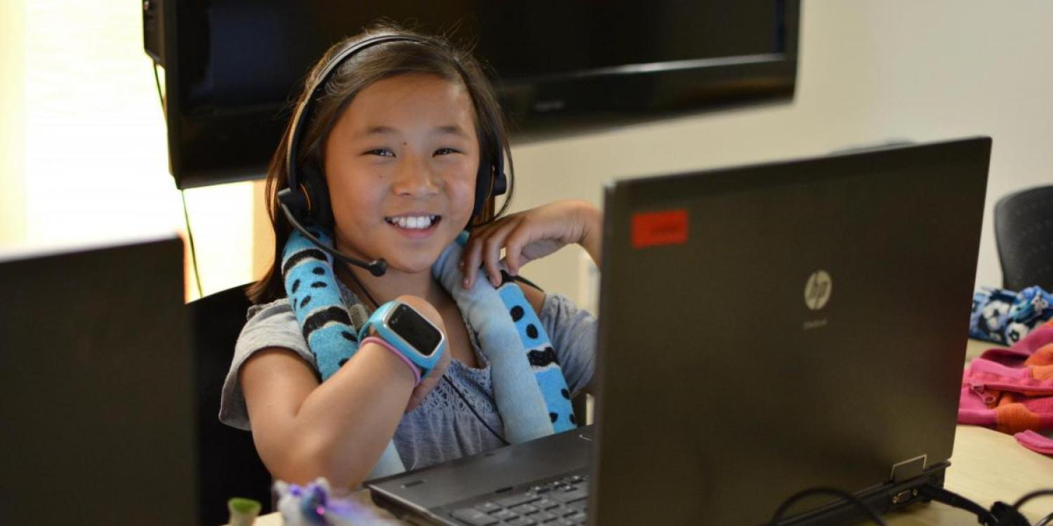 A student sits at a computer smiling