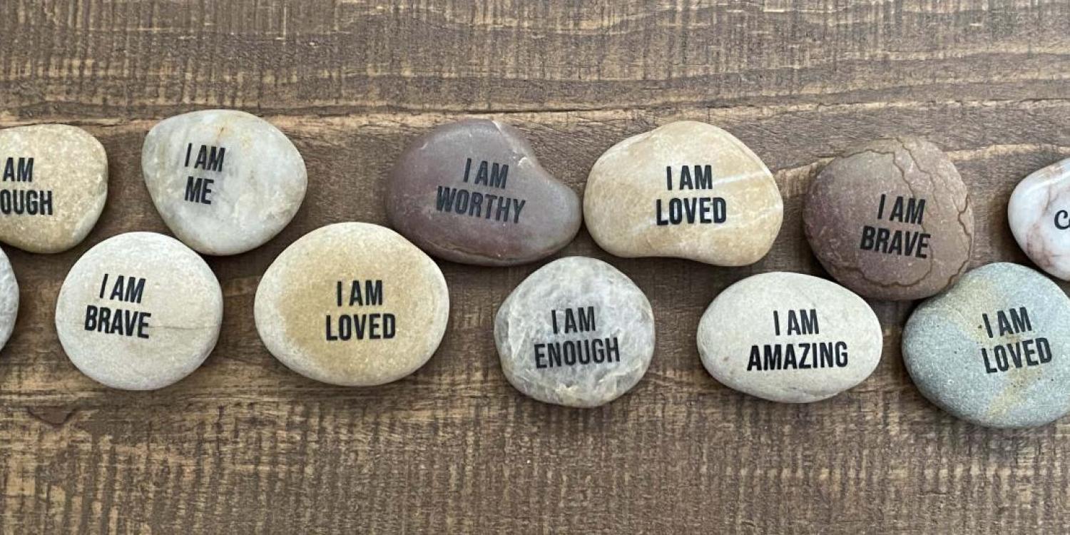 Image of rocks displaying messages of self-affirmation.