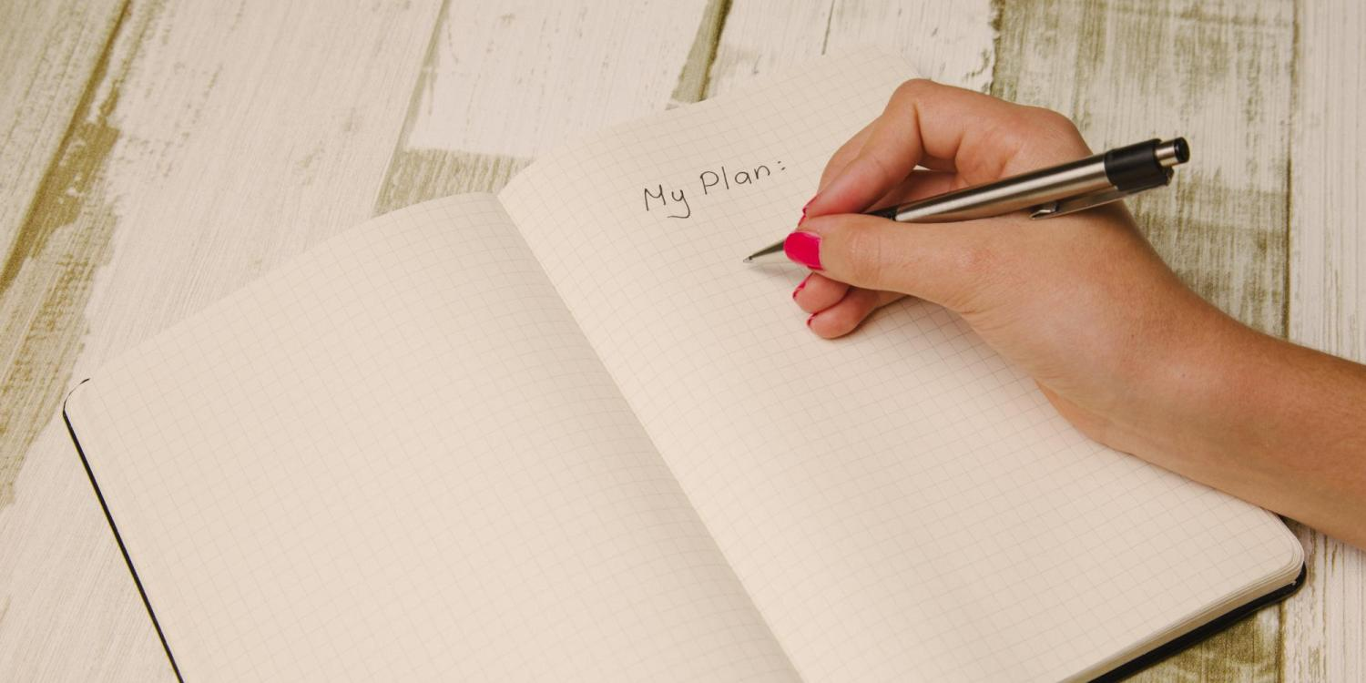Person writing down plans for New Year's resolutions
