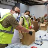 Stock image of workers packing food boxes during the COVID-19 pandemic