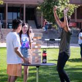 students playing giant Jenga at an outdoor Fall Welcome event in 2019