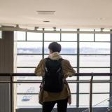 Person looks out window at airport