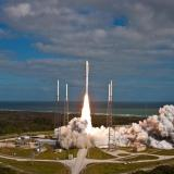 The Atlas V rocket takes off from a launch pad.