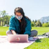Student in mask working on laptop outside