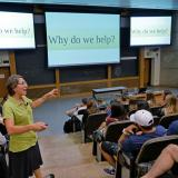 "Wroe speaks to a group of students in a classroom, the screen says, ""Why do we help?"""
