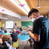 Ricardo Reyes takes air quality measurements from the back of a classroom filled with kids