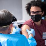 Richard Biggs, 20, an evolutionary biology major at CU Boulder, gets his first dose of the Moderna vaccine from Dr. Laird Wolfe. (Photo by Glenn Asakawa/University of Colorado)