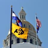 A CU, Colorado and United States flag at the Denver capitol building.
