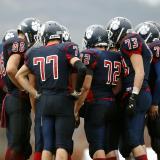 High school boys huddle during football game