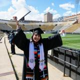 Valeria Ayala Alonso celebrates after getting her photo taken at Folsom Field during Grad Appreciation Days events