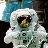 NASA astronaut services the Hubble Space Telescope from orbit.
