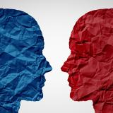 Stock image of a blue head and red head facing off