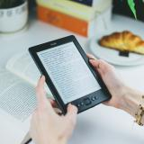 Woman reads book on Kindle e-reader