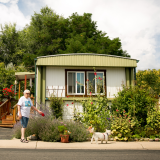 A woman walks in front of a manufactured home.