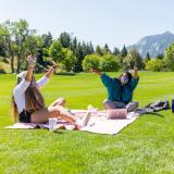 Students in masks sitting on blankets on grass
