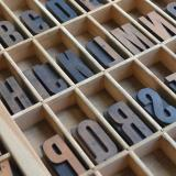 Letterpress letters are resting in a wooden box.