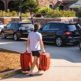 Student carrying luggage on campus