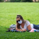 student lying in grass on campus