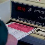 A person slides a ballot into an electronic voting machine.