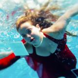 Woman in red dress swimming through water with floating photographs